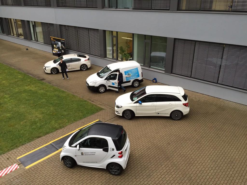 In einem Innenhof der RUB konnten die Teilnehmer des Workshops die Elektroautos der Projektpartner besichtigen, hier die Autos von Rüschkamp und Lueg. Rüschkamp zeigte den bewährten Opel Ampera und den neuen Peugeot Partner Electric