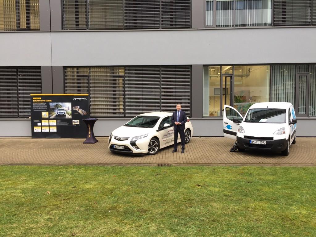 Joan Hendrik Rüschkamp zwischen den Vom Autohaus Rüschkamp ausgestellten E-Fahrzeugen. Beide Autos können momentan zu Sonderkonditionen erworben werden.