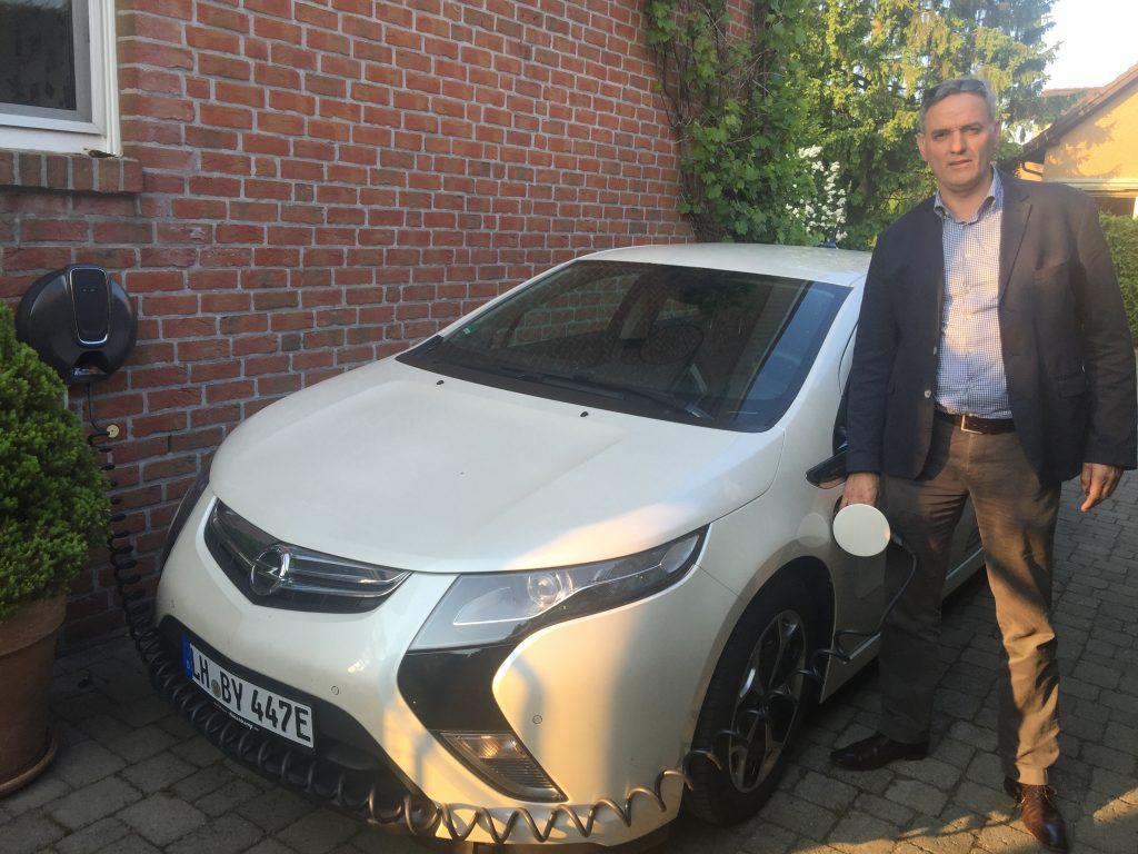 Amandus Petrusch aus Lüdinghausen mit seinem Opel Ampera un der Wallbox von Opel