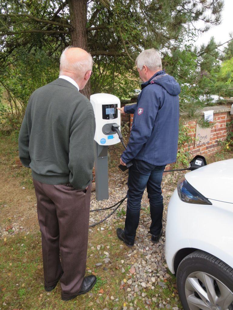 Dietrich Koch, der Sponsor der Ladesäule, und Dieter Ruhe von thenewmotion nehmen die neue Ladesäule in Betrieb. Auch eine Drehstromsteckdose steht für weitere Fahrzeuge zur Verfügung.